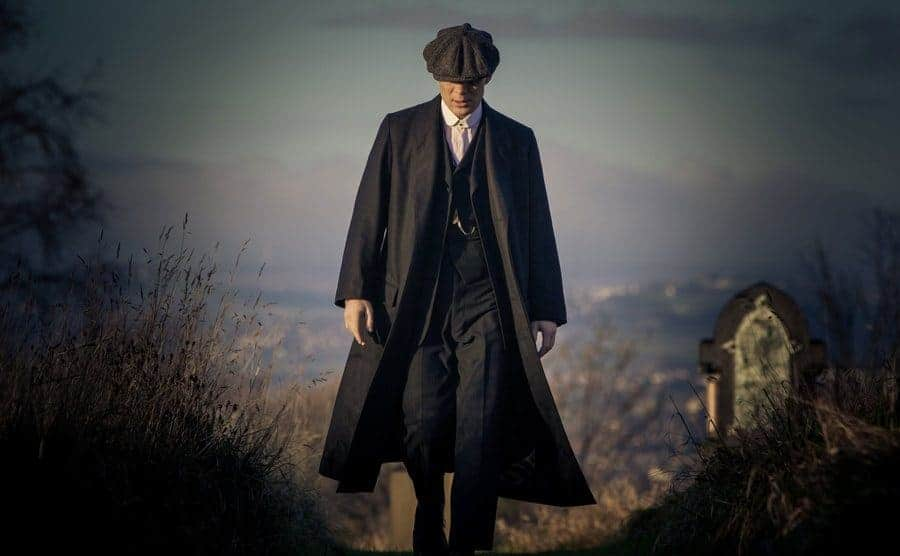 Tommy Shelby walking with his head down, his face hiding behind his cap.