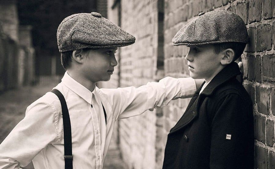 Tow little boys dressed in gangster-type clothing leaning on a brick wall.