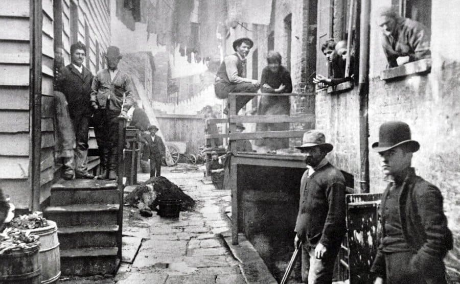 Photograph of Bandits' Roost by Jacob Riis, young men in a smoky alleyway