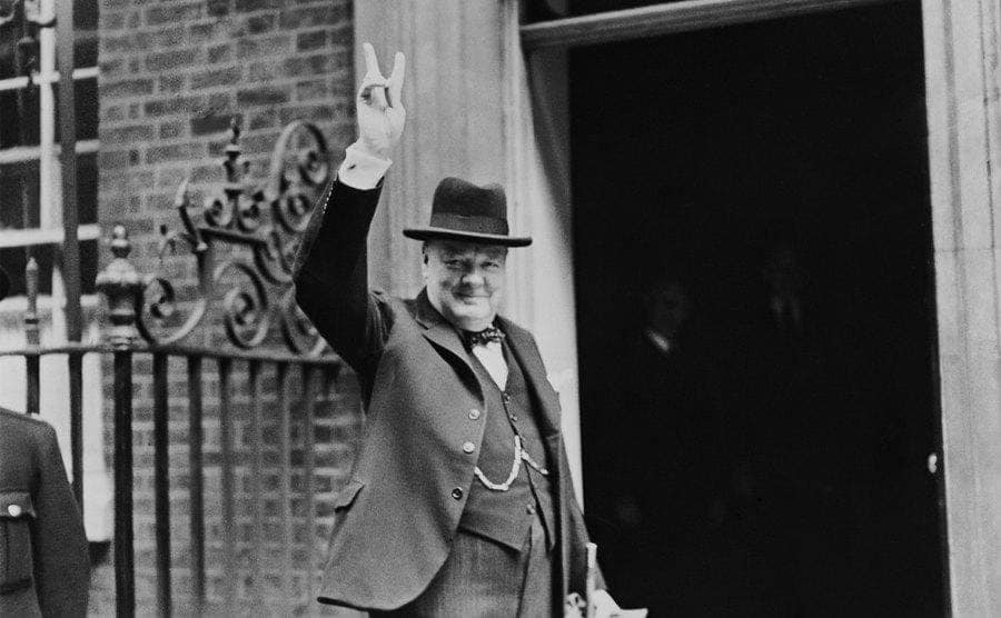 Prime Minister Winston Churchill outside 10 Downing Street, gesturing his famous 'V for Victory' hand signal.