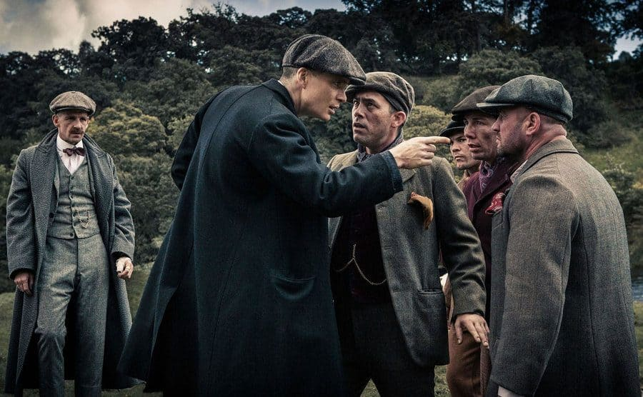 Thomas Shelby pointing a threatening figure at some scared-looking men.