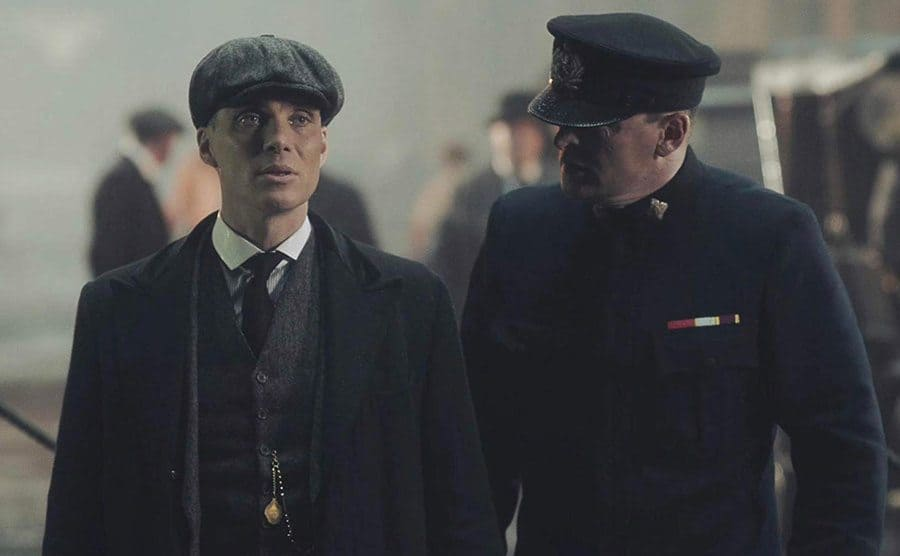 Tommy Shelby conversing with a police officer.