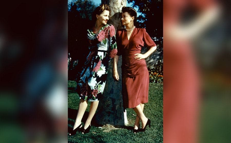 A portrait of Joan Fontaine and her sister, Olivia de Havilland, both British actresses, standing in conversation by a tree.