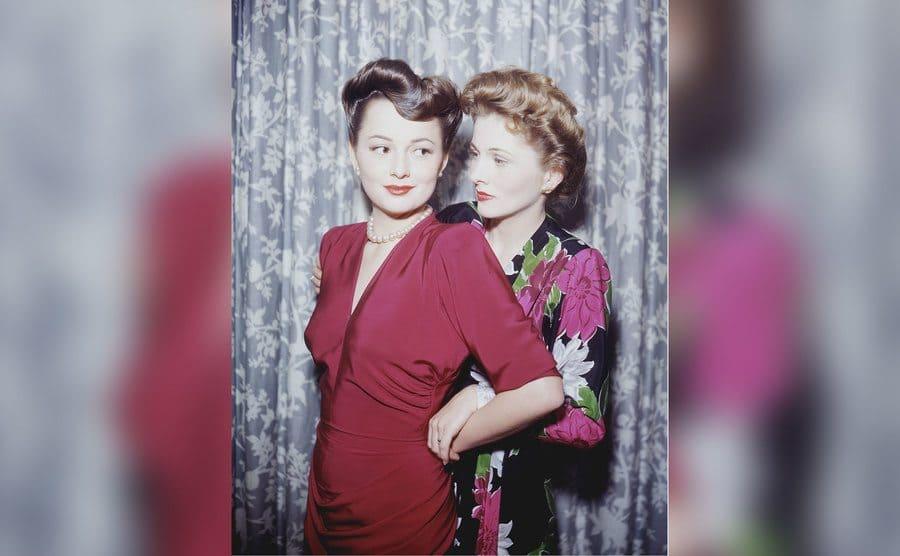 Actress Olivia de Havilland with her sister, actress Joan Fontaine standing behind her.