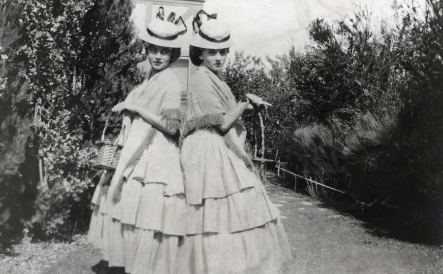Sisters Olivia de Havilland and Joan Fontaine at a party in Saratoga, California. The two young actresses are shown standing back-to-back, wearing full-length flounced dresses, hats, and shawls.