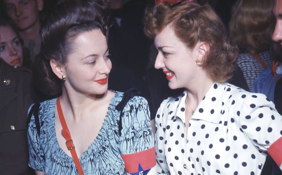 American sibling actresses Joan Fontaine and Olivia de Havilland smile at one another while attending an event at the Hollywood Canteen.