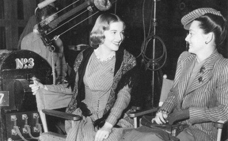 Joan and Olivia of a film set sitting in chairs behind the scenes.