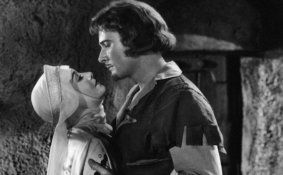 Actors Errol Flynn and Olivia de Havilland embrace in a still from 'The Adventures of Robin Hood'.