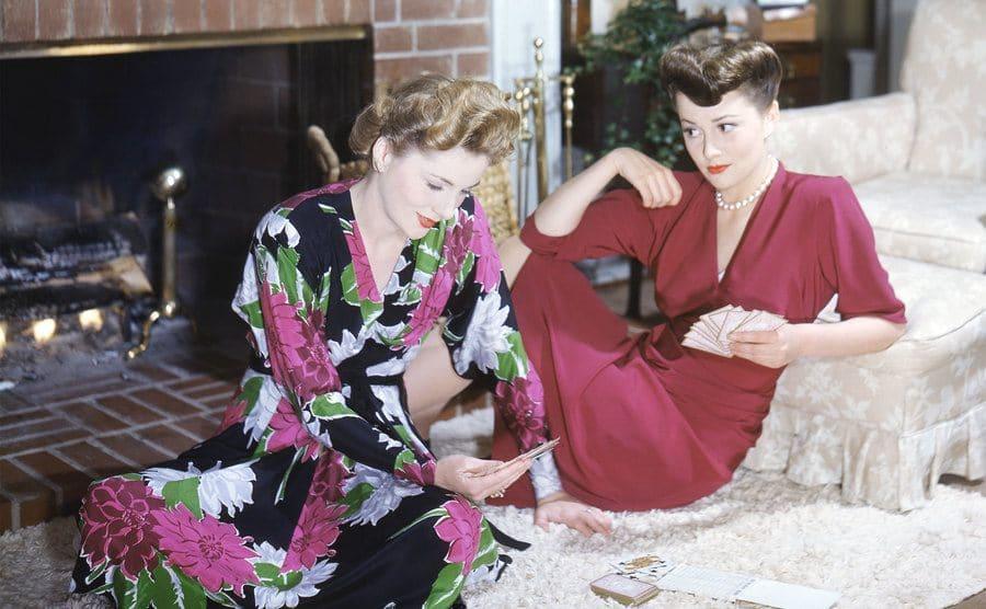 Actress Olivia de Havilland plays cards with her sister, actress Joan Fontaine, circa 1945.