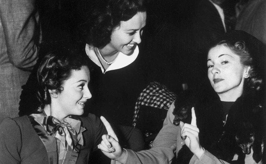 British actress Olivia de Havilland in a restaurant with her sister Joan Fontaine (right) and American actress Margaret Lindsay.