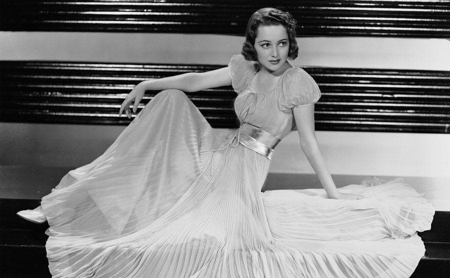 British-born actress Olivia de Havilland is wearing a full-length pleated gown with a gathered waist and puffed sleeves.