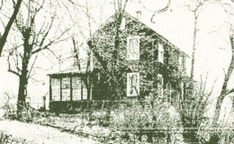 A house in the woods with a broken front porch and windows
