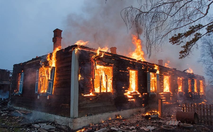 A house on fire in a woodsy area