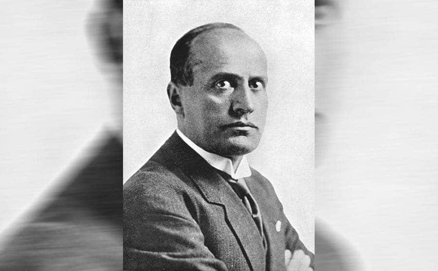 A black and white portrait of Benito Mussolini