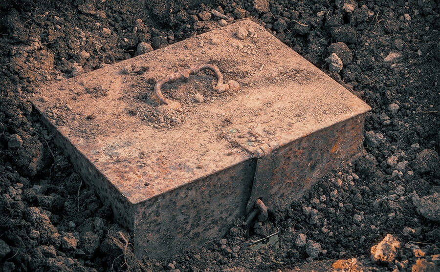 An old, buried box sticking out of the dirt