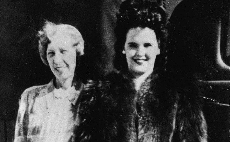 Elizabeth Short wears a fur coat and stands with her mother, Phoebe Mae Short.