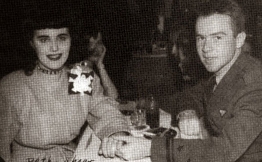 Short out to another dinner date, she sits at a table as her date holds her hand.