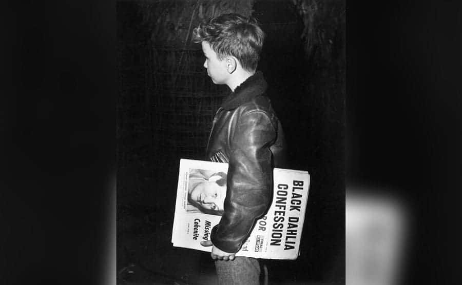 A newspaper boy in New York City, carrying an edition with the headline 'Black Dahlia Confession'.