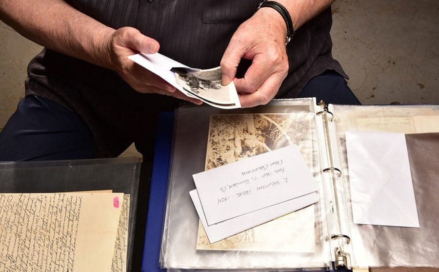 The hands of a man examining the evidence collected during the Black Dahlia investigation.