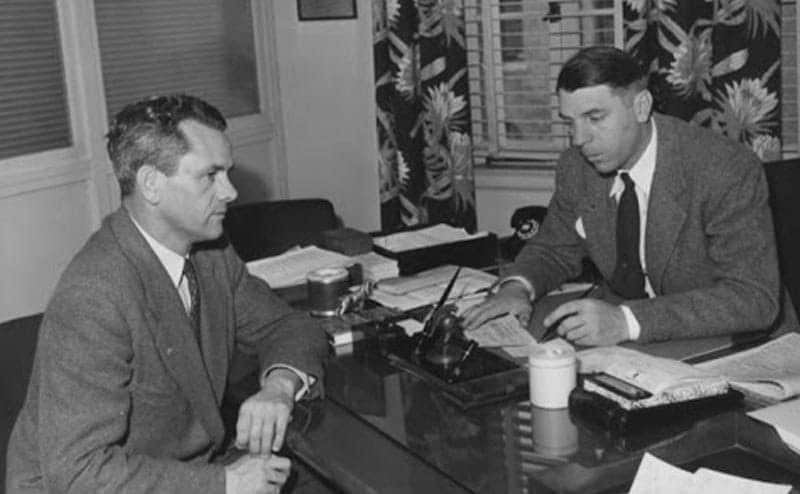 The dean of The University of Southern California is talking to another man in his office.
