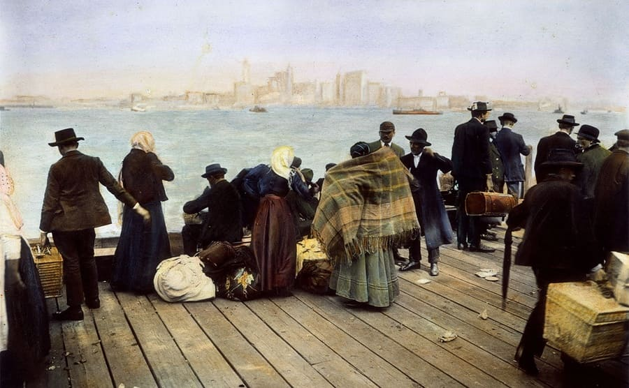 Immigrant families standing on New York Harbor who just arrived at Ellis Island