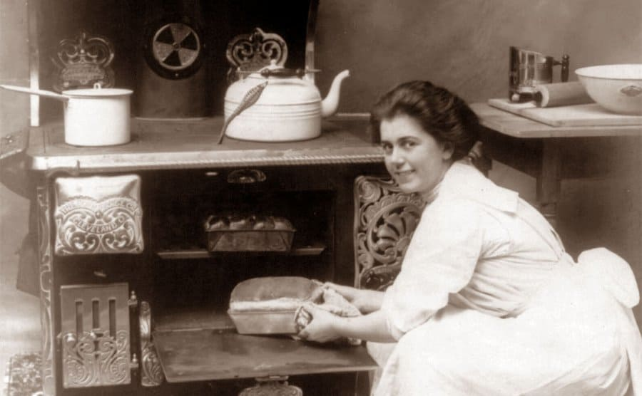 A woman placing a loaf of bread in the oven