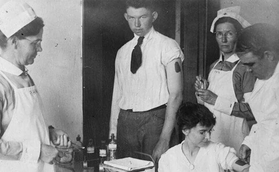 A woman providing samples with nurses and a man standing around