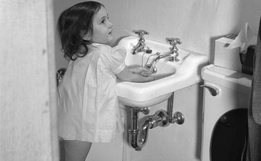 A young girl washing her hands in the bathroom in the early 1940s