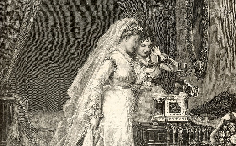A bride and her maid of honor admiring a piece of jewelry on her wedding day