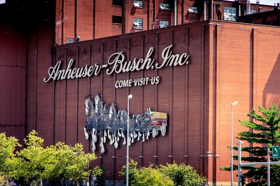 A photograph of the Anheuser Busch brewery with a large sign on the brick wall.