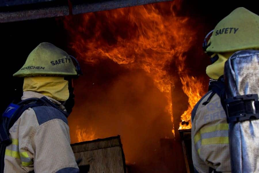 A photograph of firefighters watching flames take over a house.