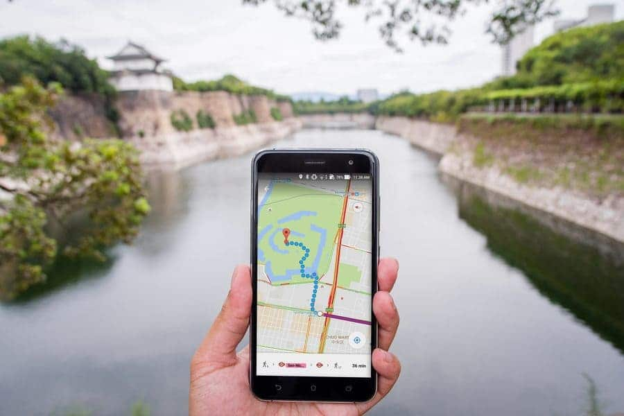 Someone is holding a phone while using Google Maps in his hand near the river in Japan.