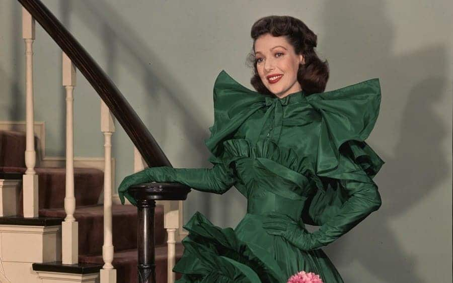 Loretta Young standing at the foot of the stairs.