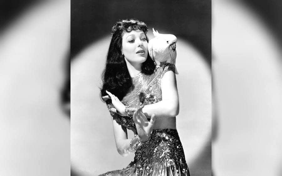 Loretta Young dancing with a cockatoo on her shoulder