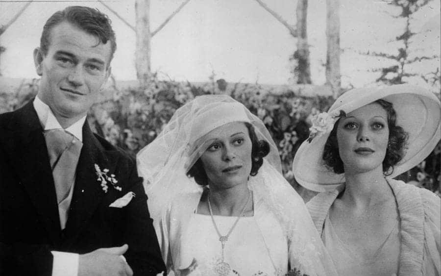 Film actor John Wayne on his wedding day with his wife Josephine Saenz and Loretta Young