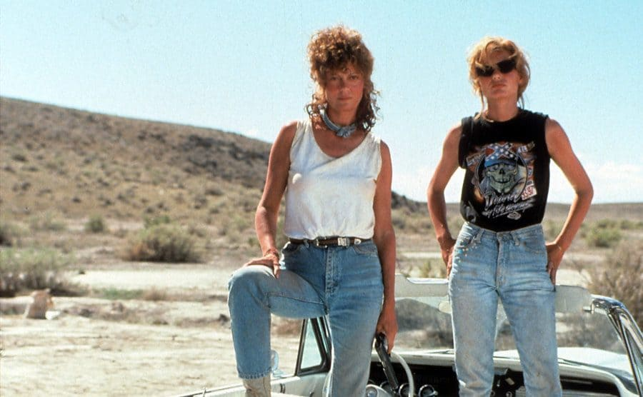 Susan Sarandon and Geena Davis standing in the convertible parked in the desert