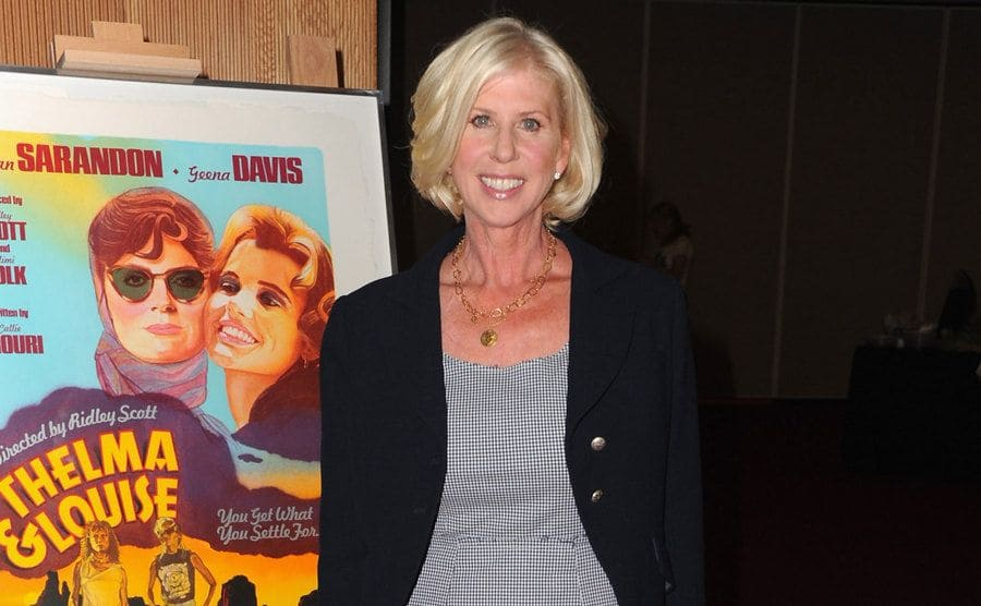 Callie Khouri on the red carpet with a Thelma and Louise poster behind her