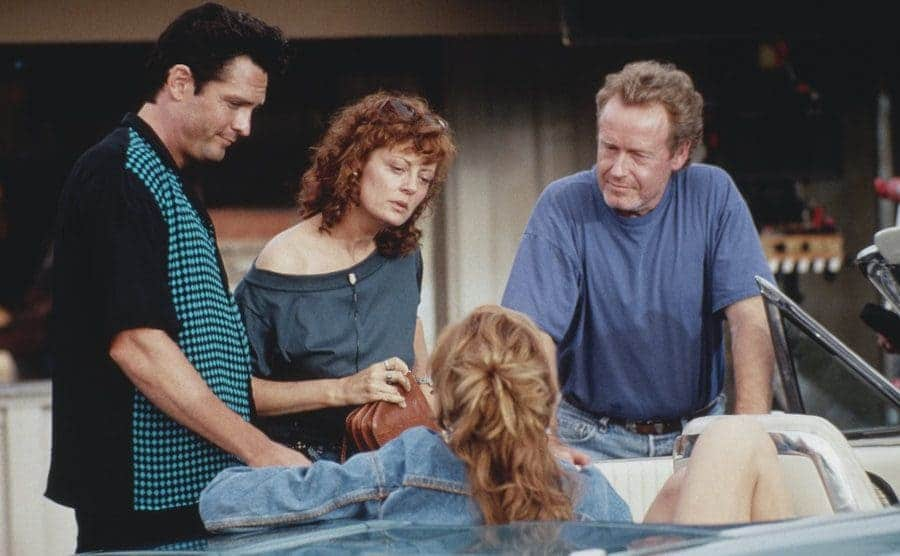Michael Madsen, Susan Sarandon, and Ridley Scott surrounding Geena Davis sitting in a car