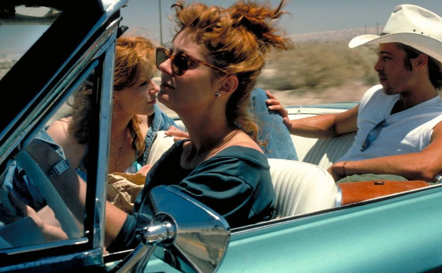 Susan Sarandon, Geena Davis, and Brad Pitt sitting in the convertible while driving in the desert