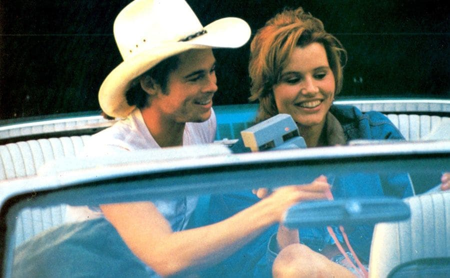 Brad Pitt and Geena Davis playing with an old camera in the backseat of the convertible