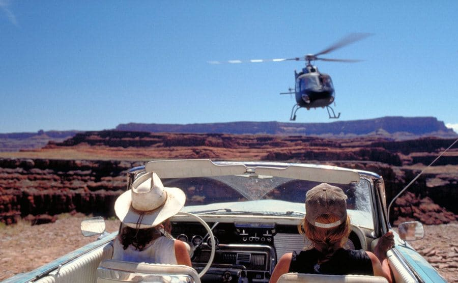 Geena Davis and Susan Sarandon looking out over the cliff with a helicopter emerging