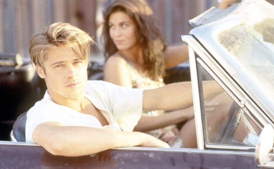 Brad Pitt posing in the driver's seat of a car