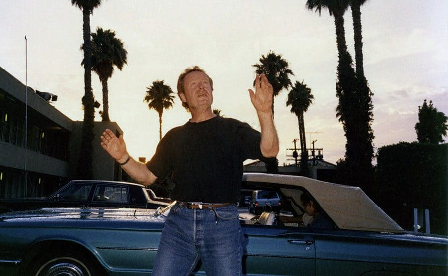 Ridley Scott making hand gestures next to the blue convertible