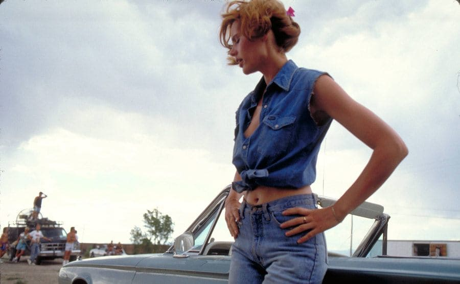 Geena Davis leaning against the convertible.