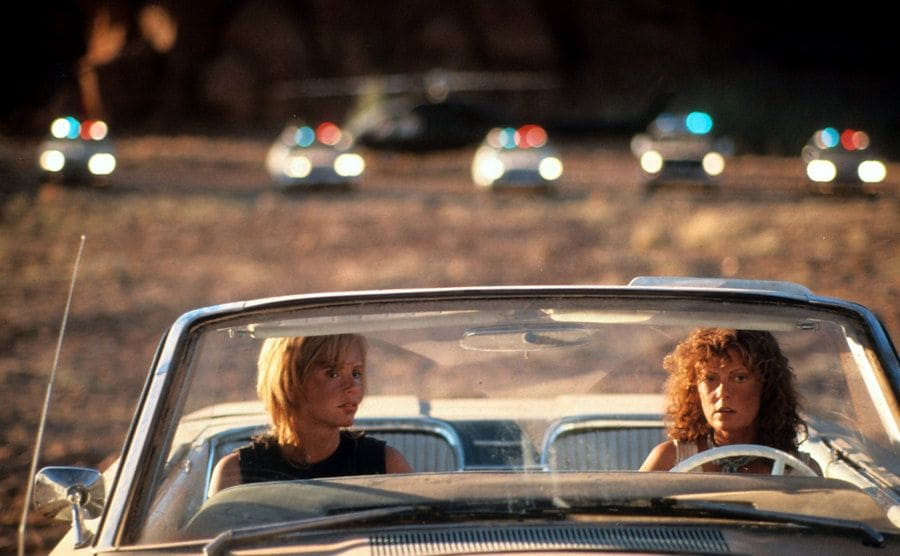 Geena Davis and Susan Sarandon sitting in their convertible with cop cars behind them lights flashing