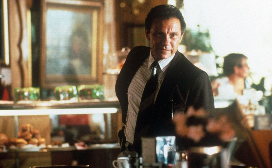 Harvey Keitel looking out into the distance while standing in a diner