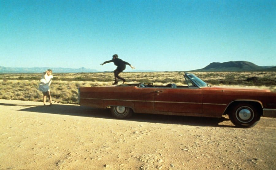 Geena Davis and Susan Sarandon jumping around their convertible in the middle of the desert