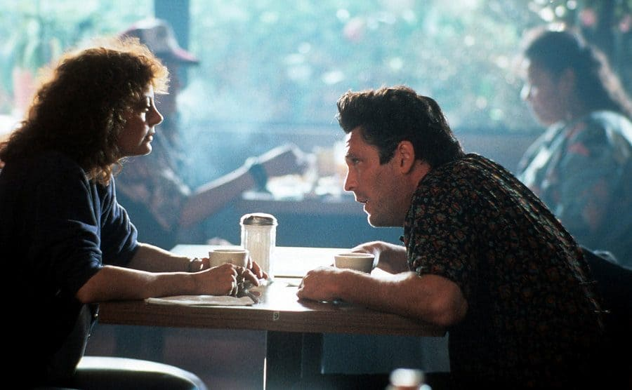 Susan Sarandon and Michael Madsen sitting in a diner drinking coffee