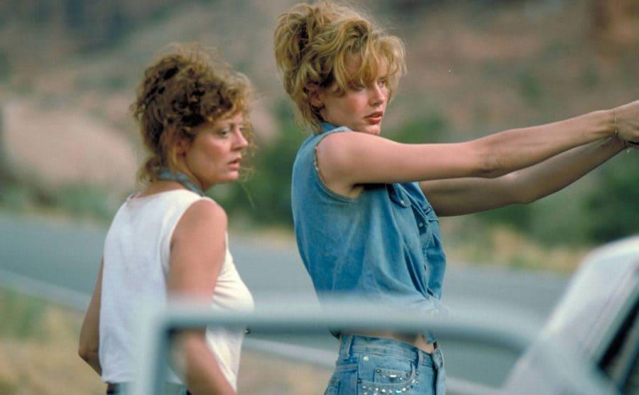 Susan Sarandon and Geena Davis standing by their car