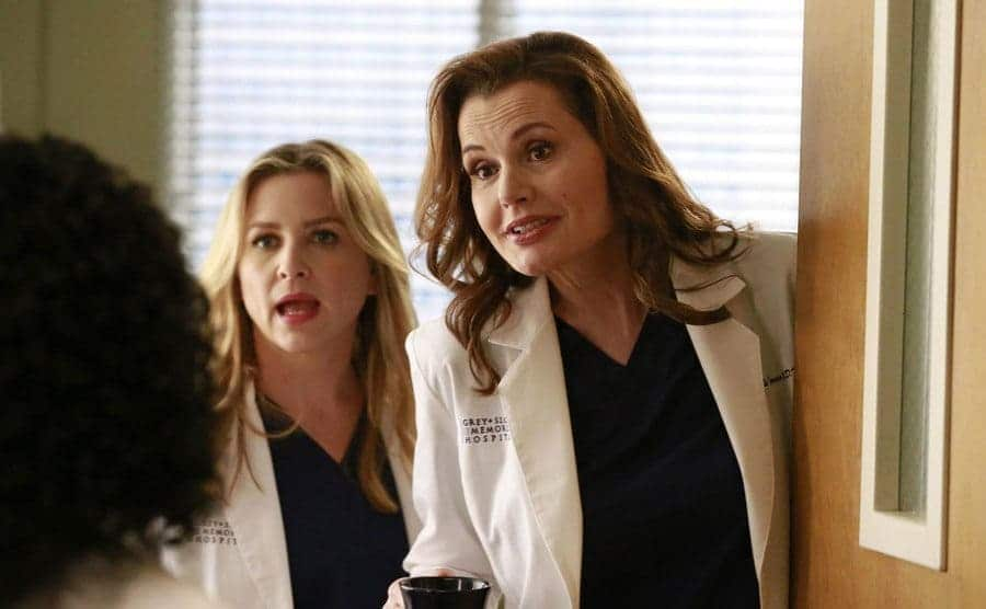 Jessica Capshaw and Geena Davis sticking their heads out of a door in a hospital in a scene from Grey's Anatomy